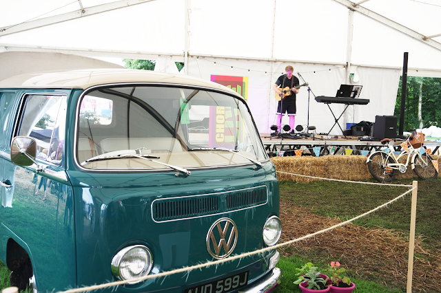 a young male singer on stage and a teal volkswagen camper van in a white marquee