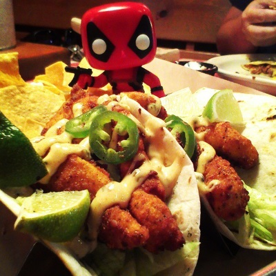 A tiny bobbleheaded Deadpool--a person in a form-fitting red and black costume--hovers behind two catfish tacos.