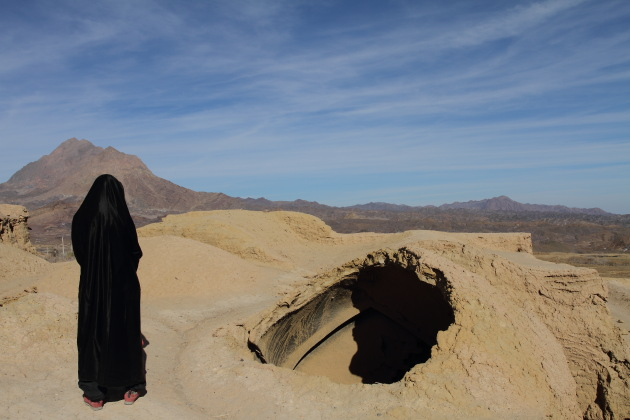Tourist in Abaya enjoying the caving in of houses at Kharanaq, Iran