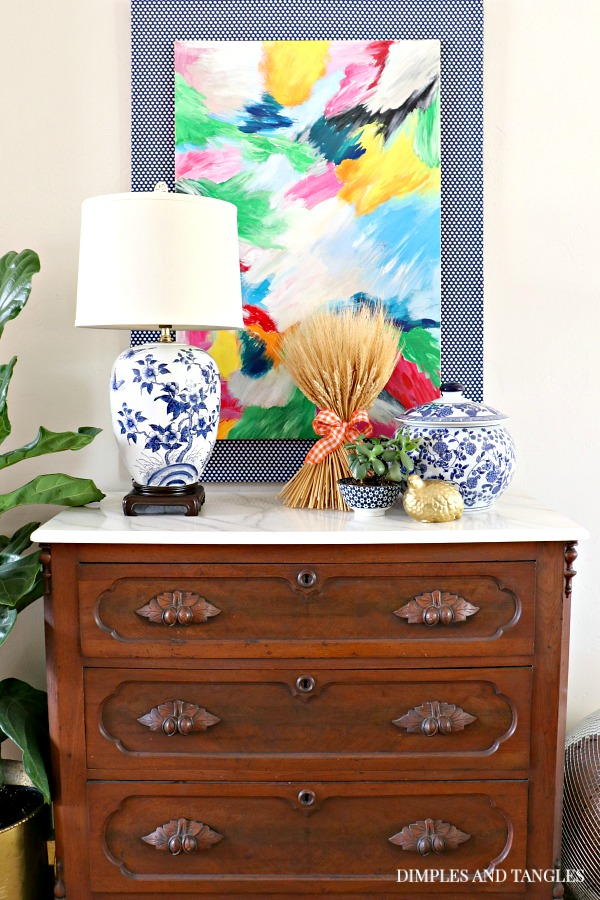 antique chest with marble top, blue and white lamp, abstract art, fall decorations