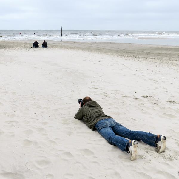 Blickwinkel, Motivsuche, Fotograf liegend im Sand
