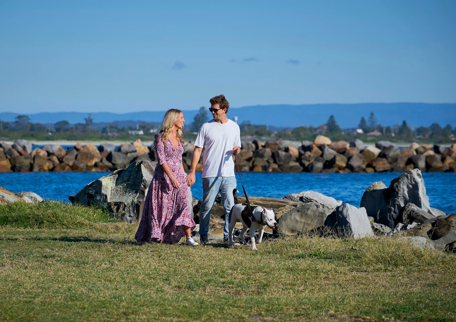 A young woman and man walk along Lake Macquarie's shore walking their dog on a leash