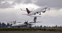 A Delta jet takes off in view of an Alaska Airlines plane that just landed Wednesday, Dec. 16, 2015, at Seattle-Tacoma International Airport. A proposed emissions standard for international aviation was approved Monday. (Credit: AP Photo/Elaine Thompson) Click to Enlarge.