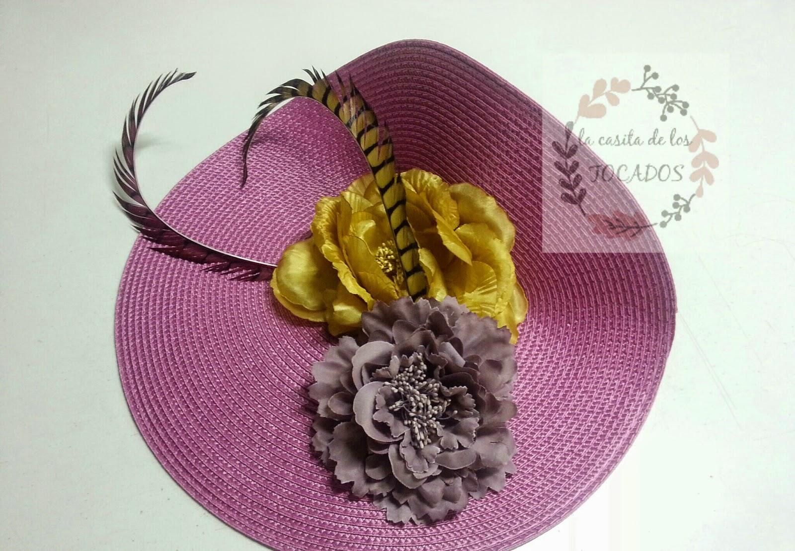 tocado grande a modo de pamela para boda en colores morado y dorado con flores y plumas de faisán