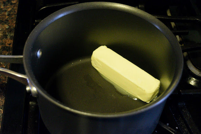 A stick of butter melting in a sauce pan.
