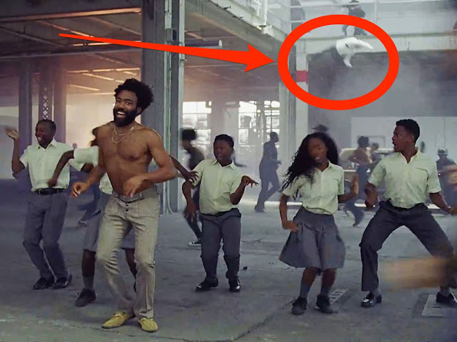 Childish Gambino's This is America - Easter egg - Watch carefully before the camera pans away and you can even see a young kid jump off the top in an apparent suicide. But nobody cares. Just another death.