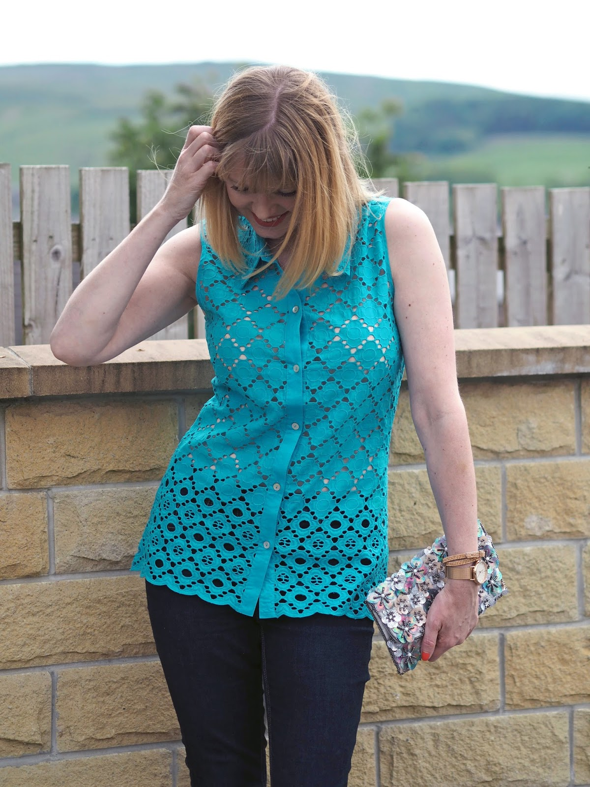 Turquoise broderie anglais top with skinny jeans and floral clutch