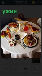 На столе приготовлен ужин на двоих. Стоят тарелки с едой и рядом салфетки и бокалы с напитками