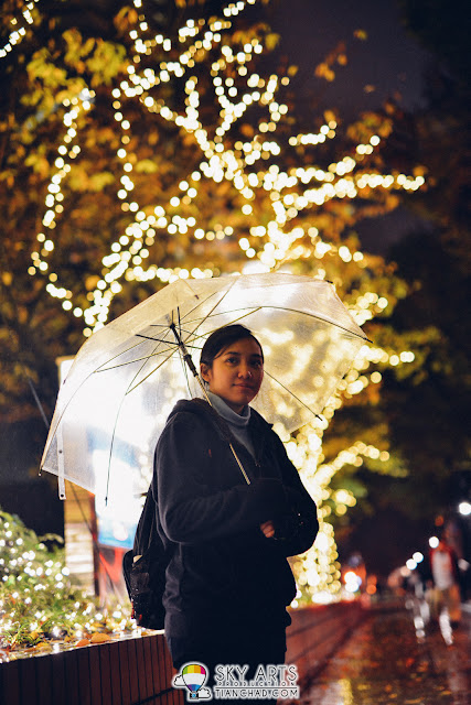 A portrait in front of Hilton Tokyo during a rainy night