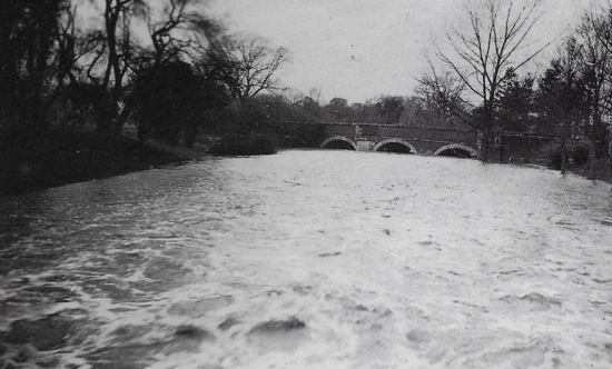 Photograph of high flood at North Mymms Park after deep snow Christmas 1927 View from the bridge in the avenue near the war memorial.
