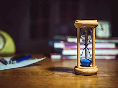 photo of an hourglass in focus, with a blurred background of pens, books and alarm clocks.