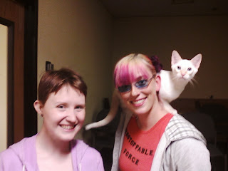 one very fair skinned female presenting person with light brown hair & a pink hoodie and a pink and purple haired fair skinned person with glasses, an orange shirt, and a white shoulder riding cat