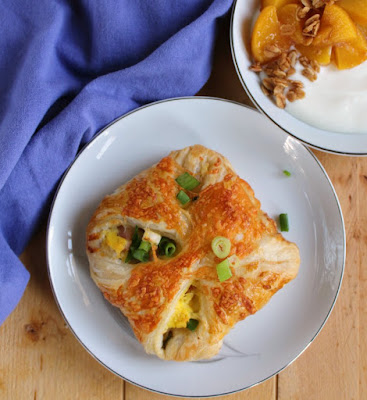 ham egg and cheese hand pie with scallions on top and a bowl of yogurt with peaches and granola in the background