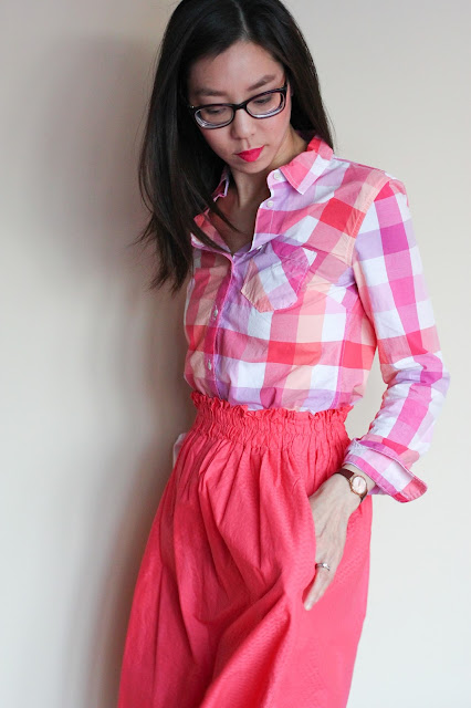 [Image of a tan skin bespectacled Asian woman wearing a plaid pink button down tucked into an elastic waist A-line coral skirt she made for herself years ago. Her hands are in the deep pockets of the skirt. She's looking down at the awesome pockets. Her dark brown hair is down.]