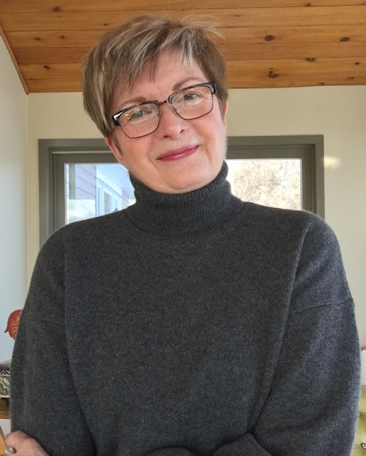 woman in grey sweater and glasses, smiling