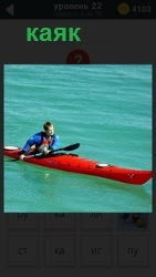 На прозрачной синей воде плывет лодка каяк человеком, который управляет веслом в одежде