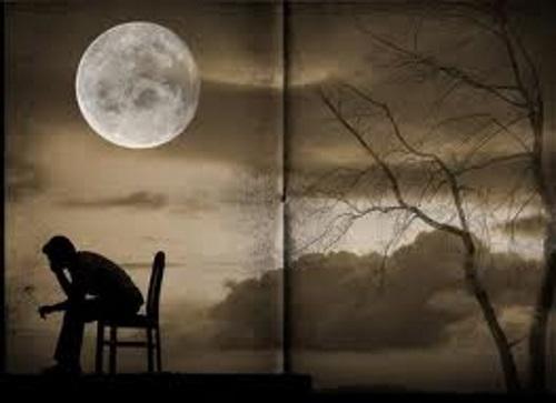 Paisagem noturna, com uma lua cheia, um jovem sentado, cabeça baixa, tristonho.