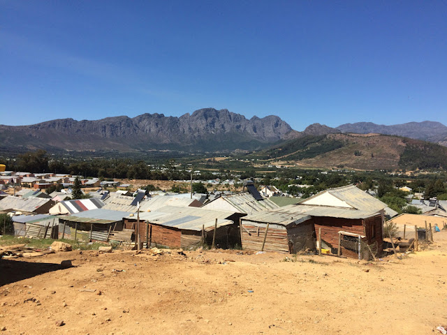 Image Attribute: Formal social housing sits adjacent to the informal settlement in Langrug. Copyright: Lauren Hermanus.