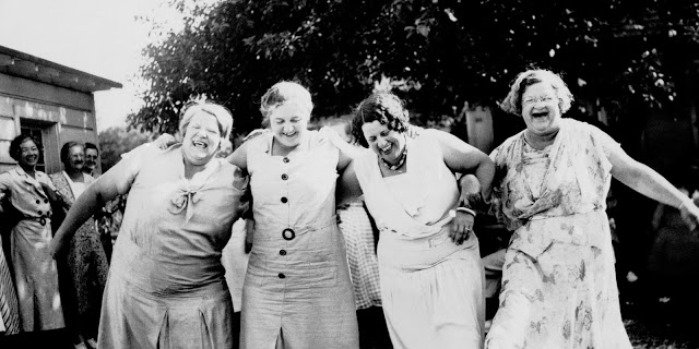 black and white photo of four middle age women in housedresses linking arms and laughing