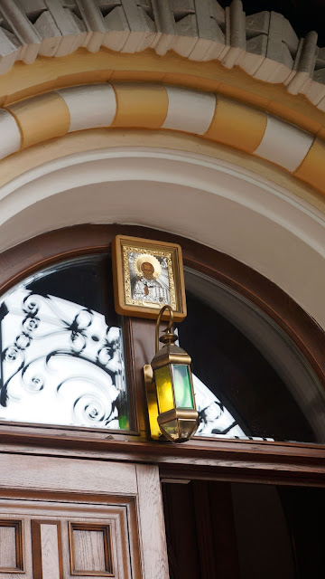 Изображение на фото иконы и фонаря в своде арки храма
