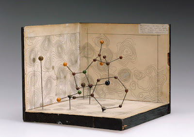 Image is of a complex structure made of wire and colored balls, on a paper and wood background.