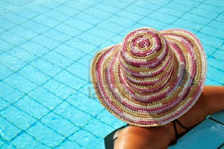 woman with a big hat in a swimming pool