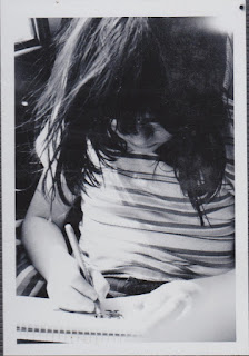 black and white photo of girl drawing in the car