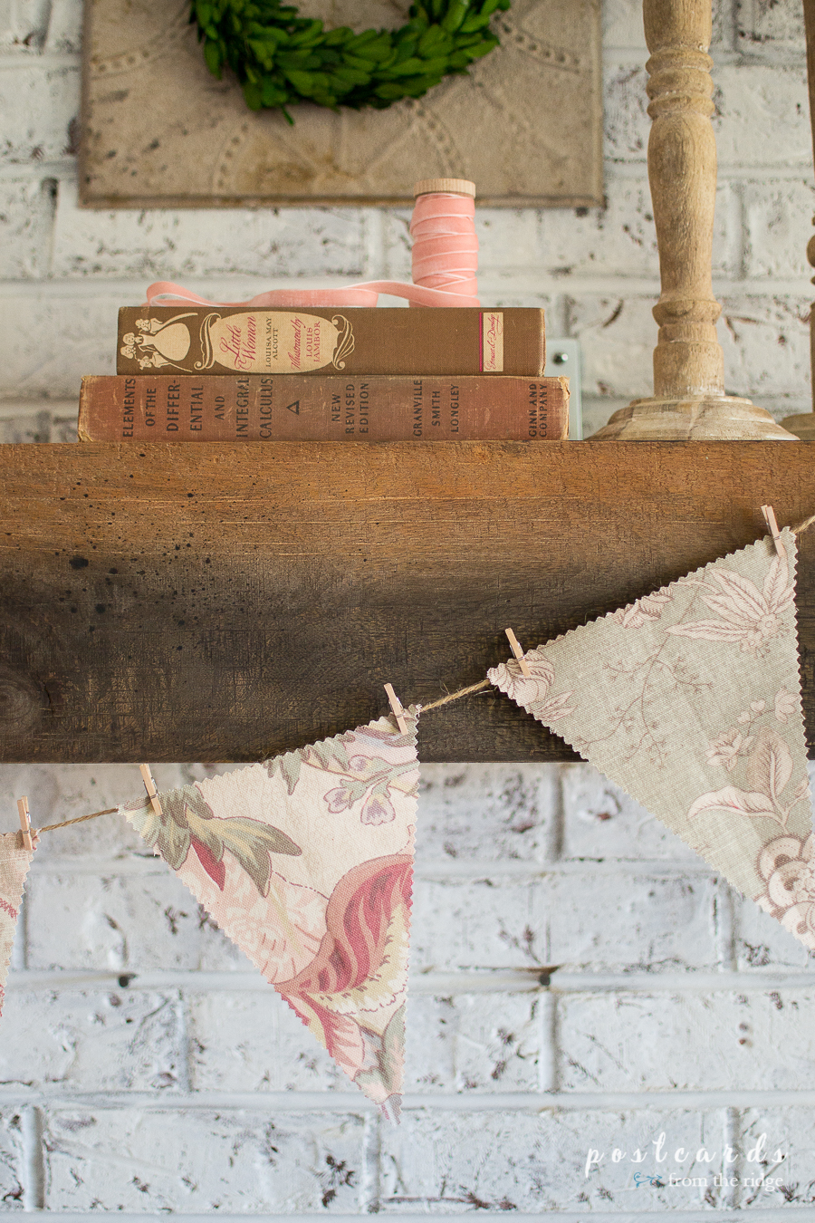 old books and blush pink velvet ribbon on a wood beam mantel