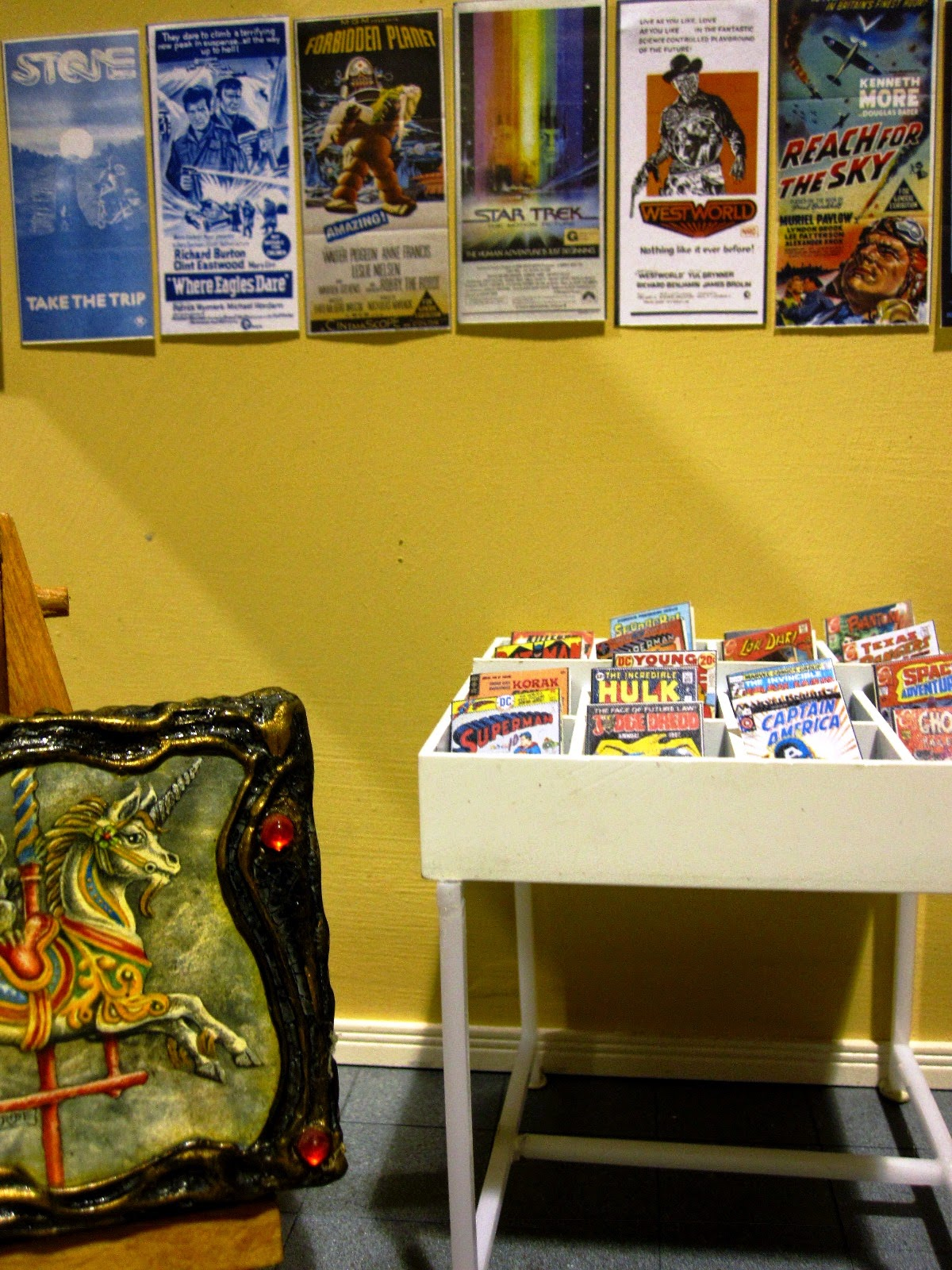 Modern miniature comic book store, interior view showing a rack of comics, a wall of posters and a fantasy art piece on an easel.