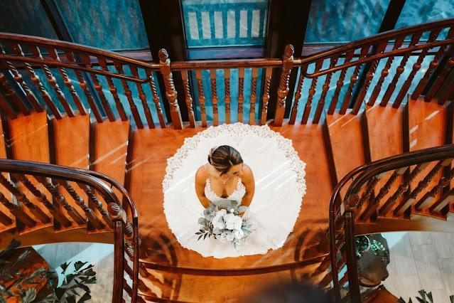 vertical shot of bride in wedding dress on stairway