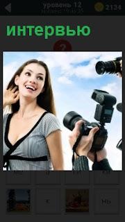 У девушки фотокорреспондент берет интервью, фотографируя её в хорошем ракурсе