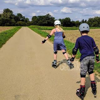 2 Kinder auf einer Straße mit Inlinescates