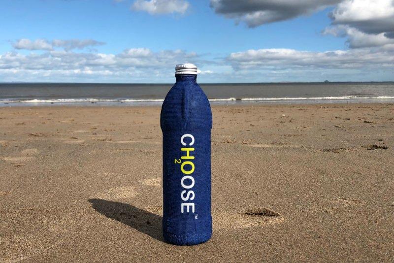 Uma garrafa azul com o logo da Ch2oose na praia