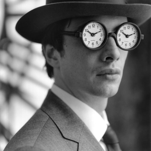 Man in suit wearing spectacles with clock faces for lenses
