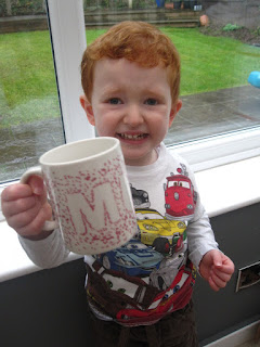 Little boy holding up a decorated mug