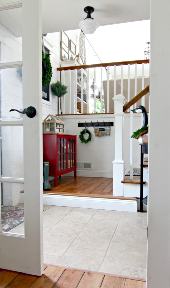 DIY entryway in split level home with wall planking and chalkboard, preserved boxwood wreath, and Ikea topiaries - www.goldenboysandme.com