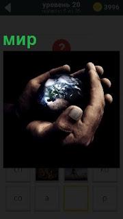В руках у человека маленькая модель земного шара, весь мир в руках