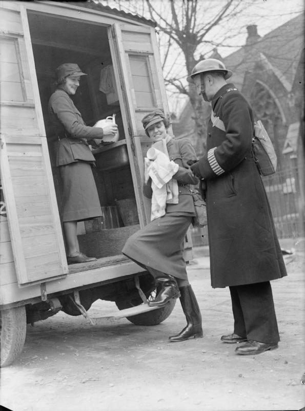 Women of the MTC WW2 - Mrs Pat Macleod and Mrs Winifred Ashford chat to a policeman as they wash up in the back of their mobile canteen, somewhere in London, 1940. A church, possibly St James's Church, Paddington, can just be seen in the background.