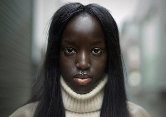 Retrato de una joven mujer de color de cabello largo usando un sueter de cuello de tortuga en la ciudad.