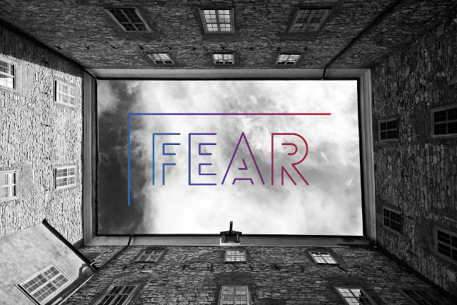 "Sky surrounded by buildings with the word ""fear"" in the middle."