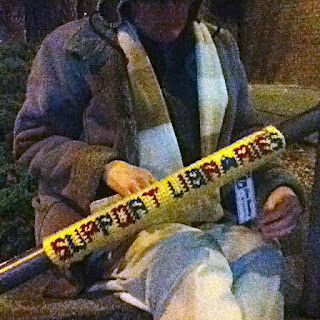 Cynthia M. Parkhill attaches 'Support Libraries' tag to railing, downtown Santa Rosa library