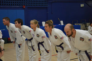 Adult martial artists doing a bow in an adult karate class