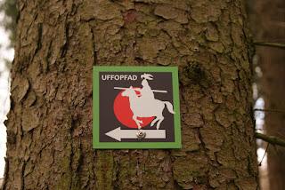 """An einem Baum hängt ein Schild. Auf dem Schild findet man einen weißen Ritter auf schwarzem Grund, darüber das Wort """"Uffopfad"""""""