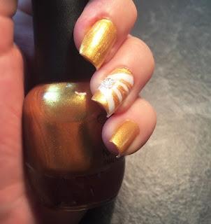 unghie oro con un dito decorativo a strisce in oro e bianco e con il brillantino al centro