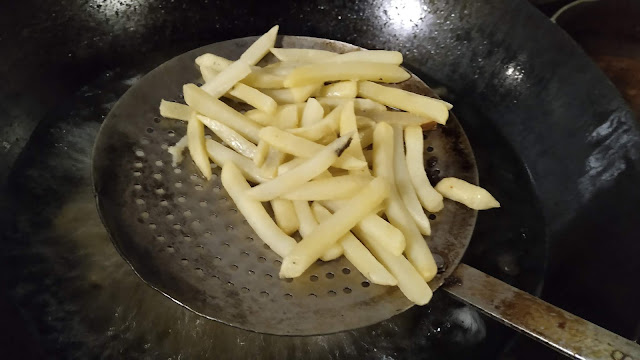 Skimming French fries using a skimmer Nearme hotels Restaurants