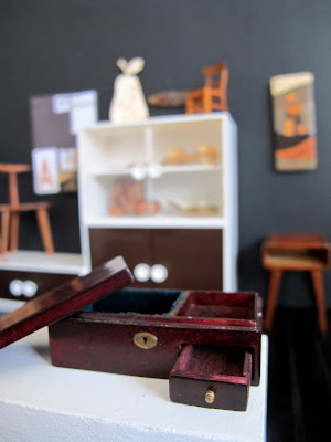 Modern dolls' house miniature plinth in a gallery, showing a wooden case with removable lid and drawer.