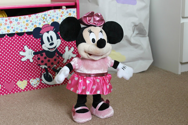An Minnie Mouse figure standing in front of a Minnie Mouse toy box