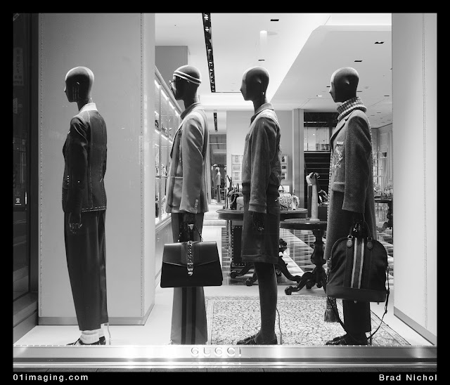 Gucci window display in Ginza, Japan, 4 people in a line with store in background.