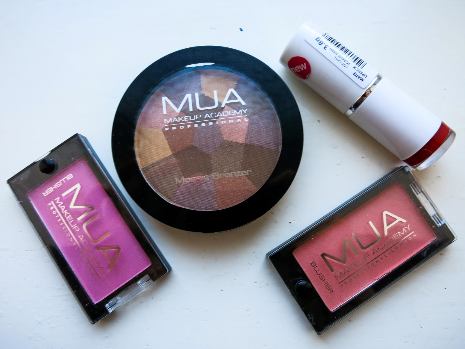 Flat-lay of MUA items; two blushes, a bronzer and a lipstick