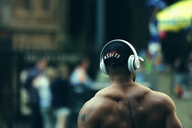 un negro afro-americano escuchando música mientras camina por la calle